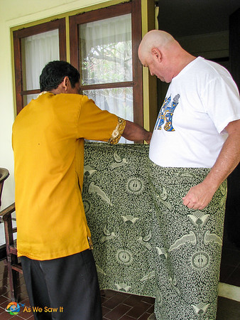 Indonesian man shows Dan how to wrap a sarong.