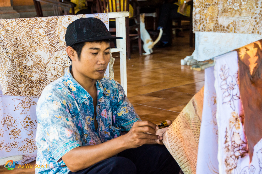 A batik artist intently focuses on his work.