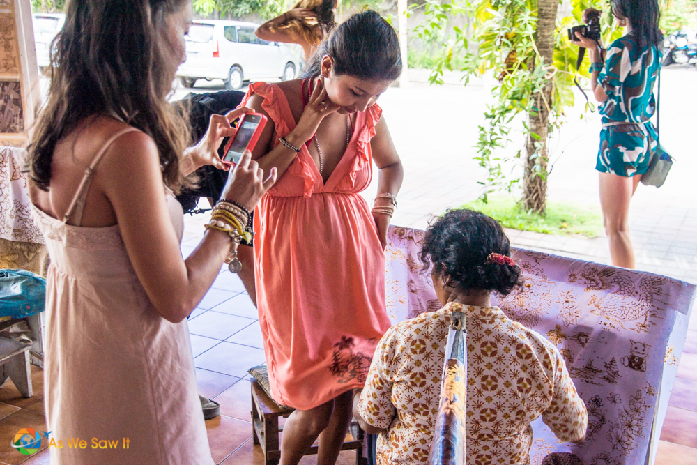 Batik artist hand-paints a dress for a tourist.