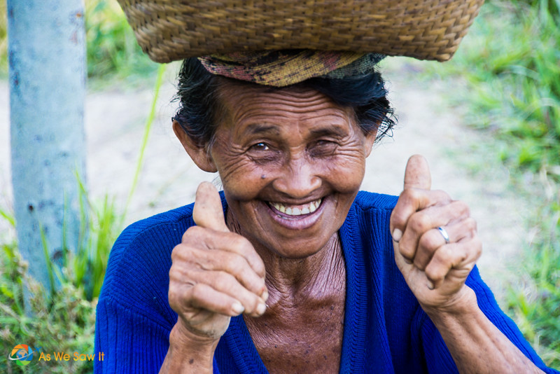 Indonesian woman in the countryside of Bali. She's got a basket on her head and giving two thumbs up.