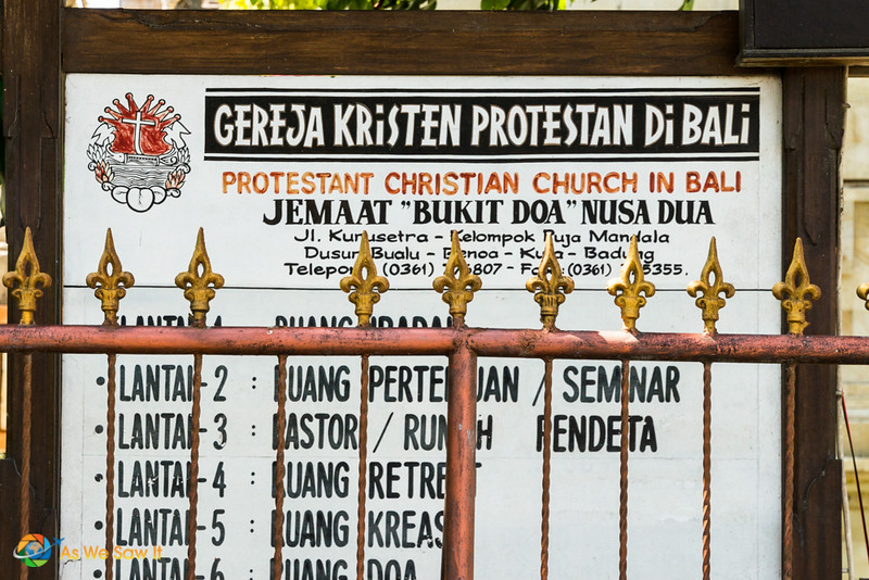 Sign in front of a protestant church in Bali. Fence in foreground. Some of the words are easy to understand.
