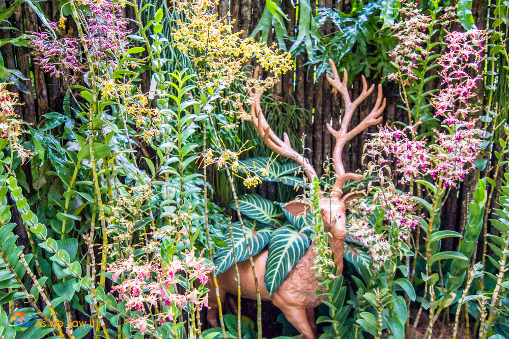 Deer sculpture surrounded by flowers