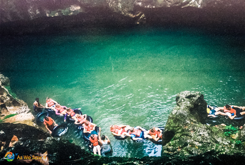 A chain of cave tubers lining up in their inner tubes to begin their trip