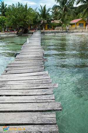 Pier onto Isla Carenero over crystal clear waters.