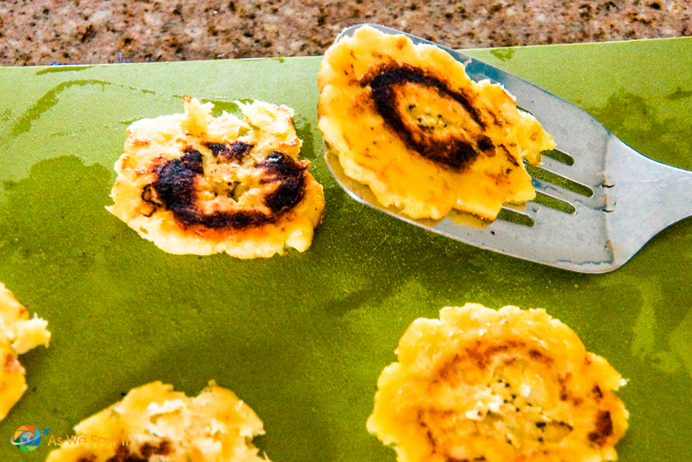 Flattened fried plantain chips on a spatula, beginning Step 4 in our easy patacones recipe