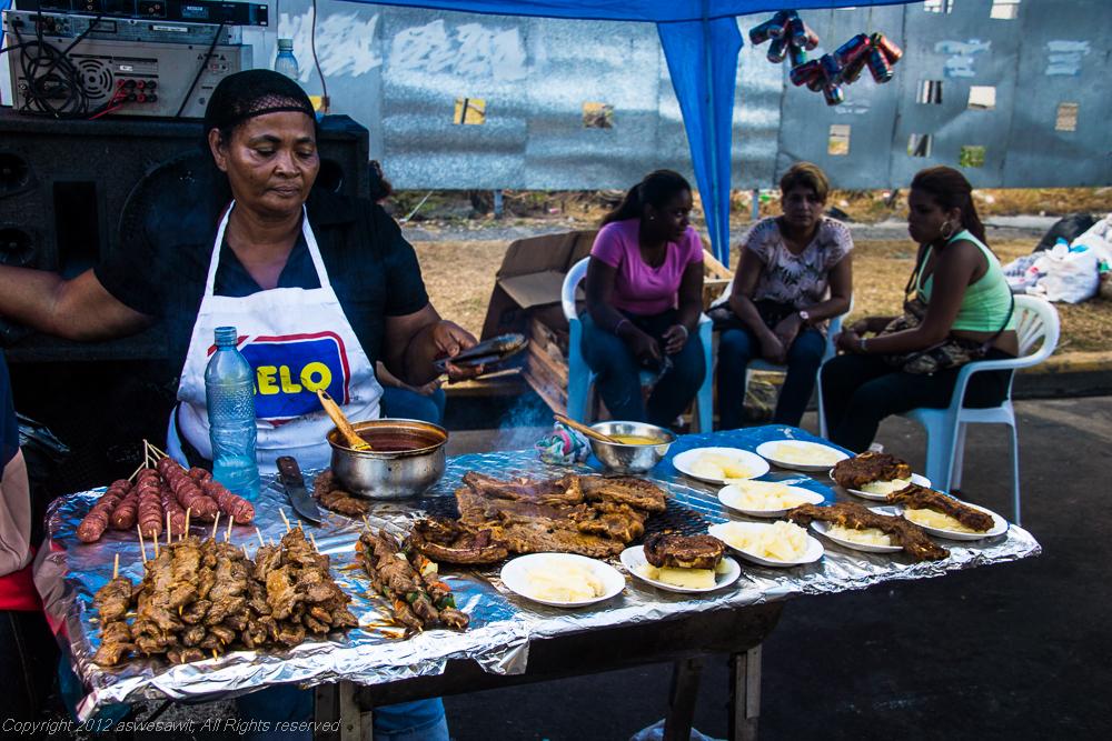 Woman sells hamburgers and other snacks during Panama carnival.