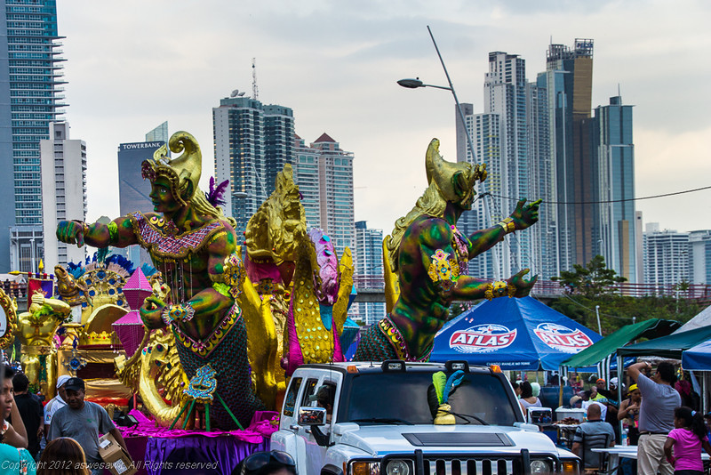 Golden carvings of women on a floats for Panama Carnival with Panama City skyline in the background