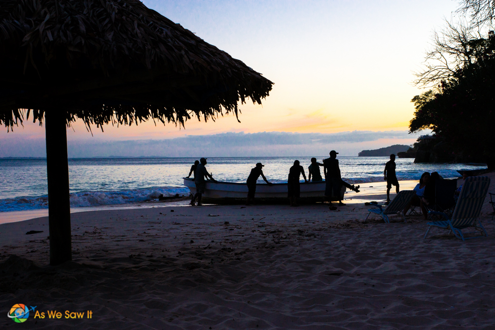 With the sun setting on the beach, locals secure the boats for the night.