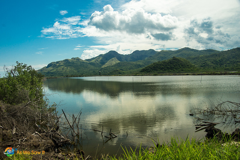 Lake used for farming shrimp with mountains in background.