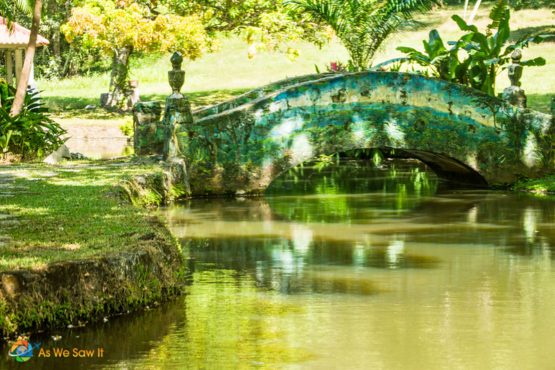 Beautifully decorated bridge over a small section of a turtle filled lake adds to the ambiance of Summit Botanical Gardens