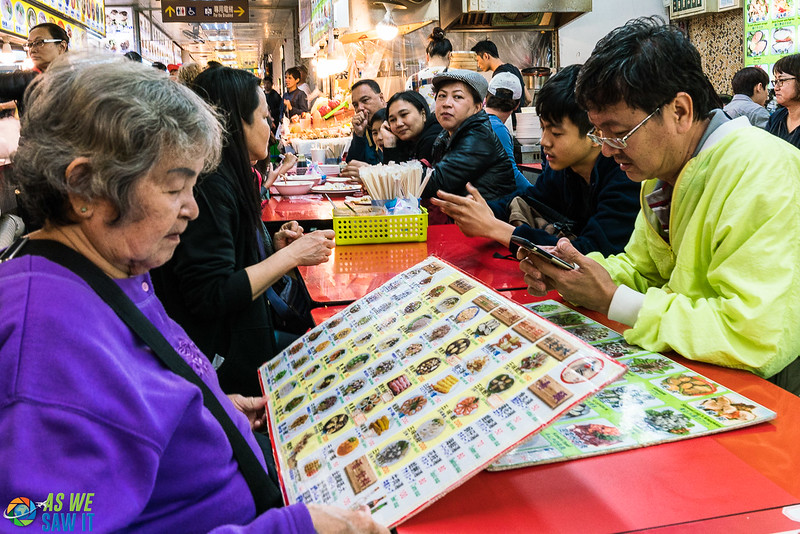 woman looking at a picture menu at Shilin Night Market food stall