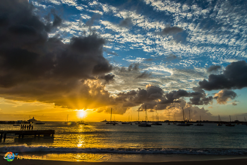 Golden sunset reflects on the water in St. Martin. Sailboats silhouetted in the background.
