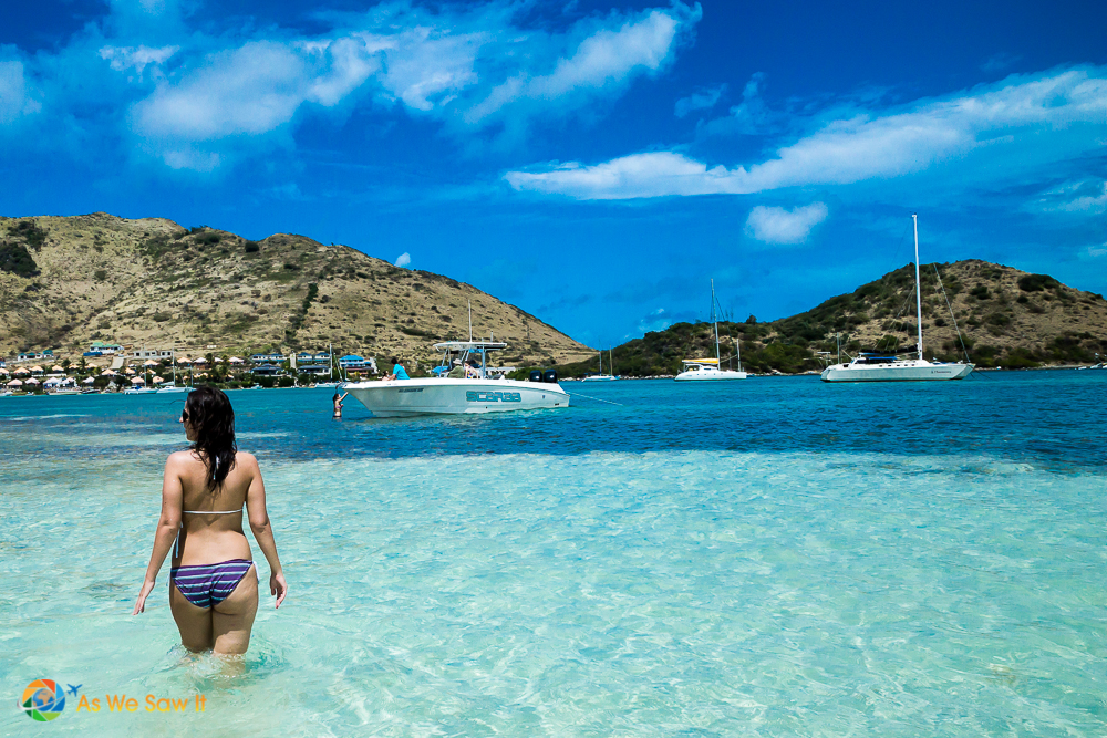 Foreground: Back view of a girl in a bikini wading on a sandbar. Background: motorboats and sailboats, anchored in the water. Low, bare hills and St Martin town in background.