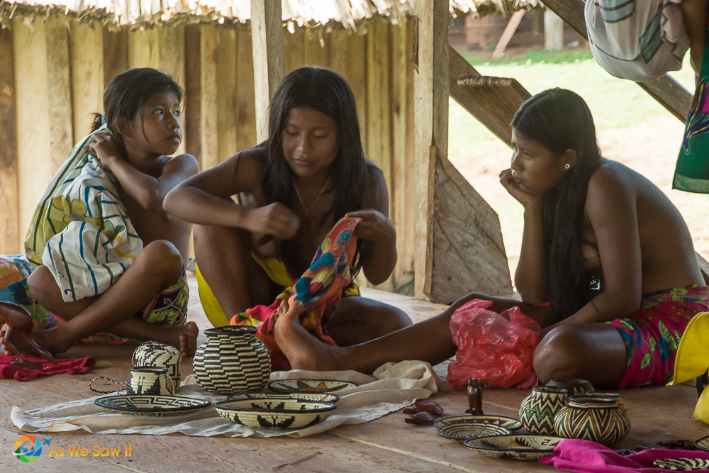 3 young Embera girls sit on the floor with their baskets
