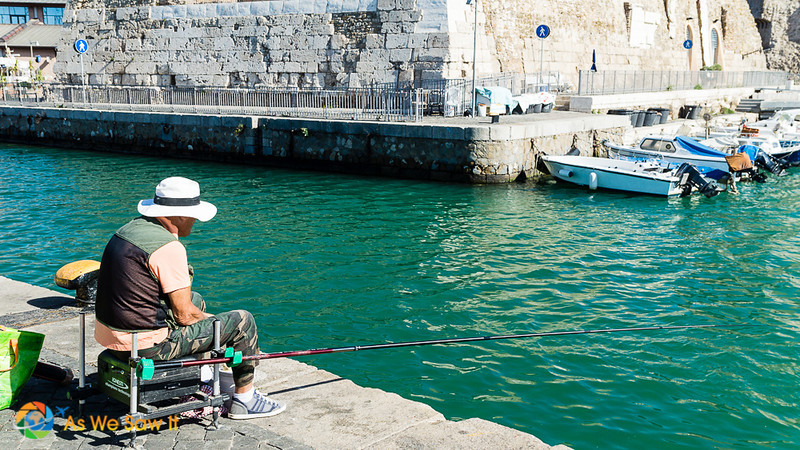 Man fishing off a dock in Civitavecchia