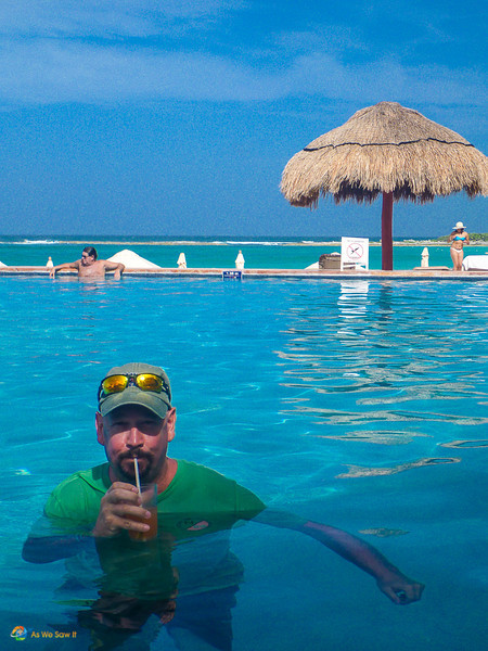 Dan sips on a drink with paper umbrella in a pool at the Hilton Resort in Cancun, Mexico