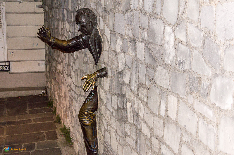 Quirky statue of a man emerging from a stone wall