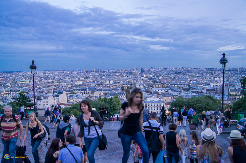 People climbing the stairs in front of Sacre Coeur. Paris skyline in background