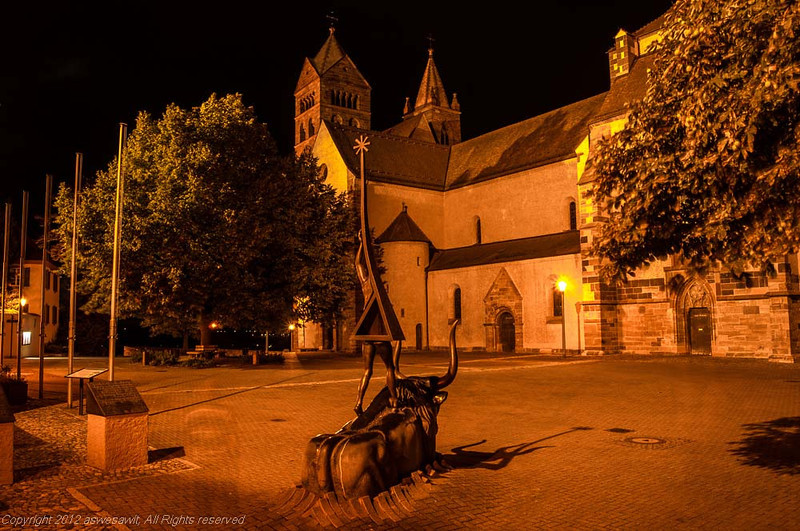Nighttime view of the courtyard of Breisach's cathedral with trees in the foreground.