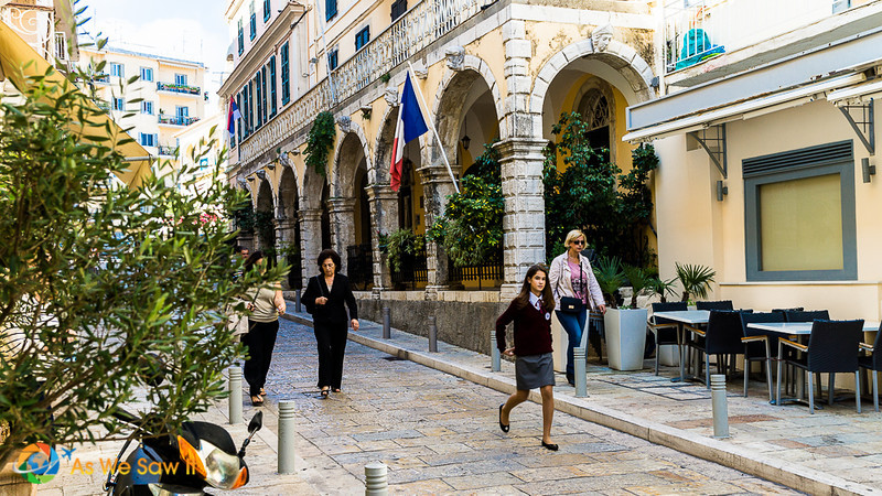people walking in front of a building with arches in Corfu town