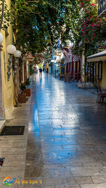 Shiny stone street in Navplion, Greece, worn by centuries of walkers and lined with shops and bougainvillea