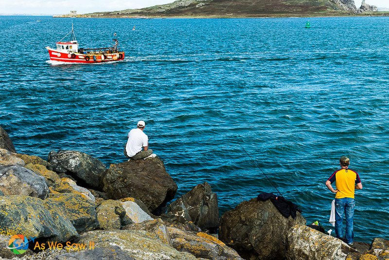 Fishing is one of the best things to do in Howth, Ireland. Here, a small fishing boat passes two fishermen on the shore, hoping for a big catch.