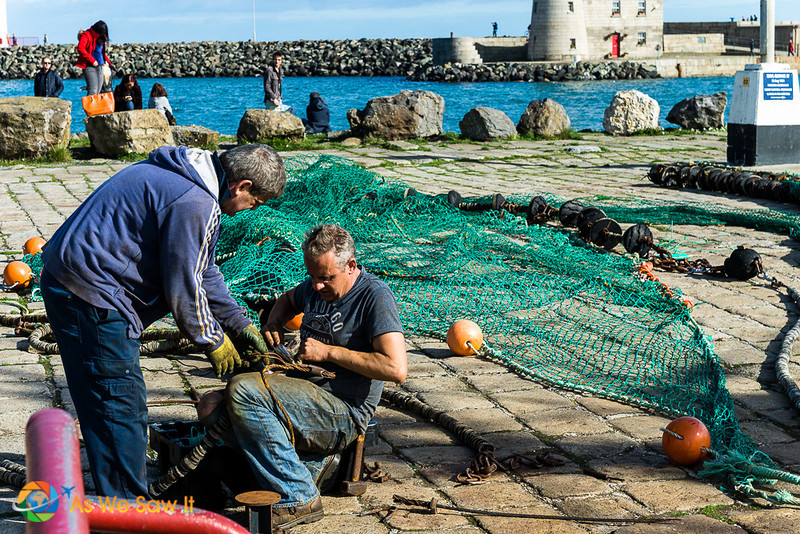 Men working on fishing nets in Howth harbor
