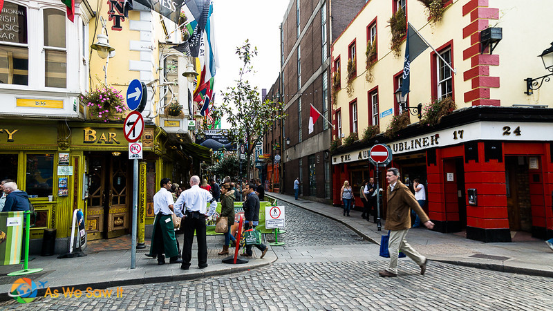 everyday life in dublin, man rushing with bag, shop proprietors talking