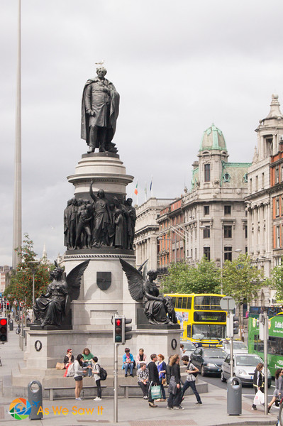 people sitting beneath statue of O'Connell, on Dublin's O'Connell street