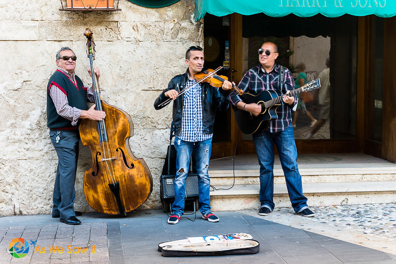 3 buskers on Corso Centocentelle, playing base, violin and guitar
