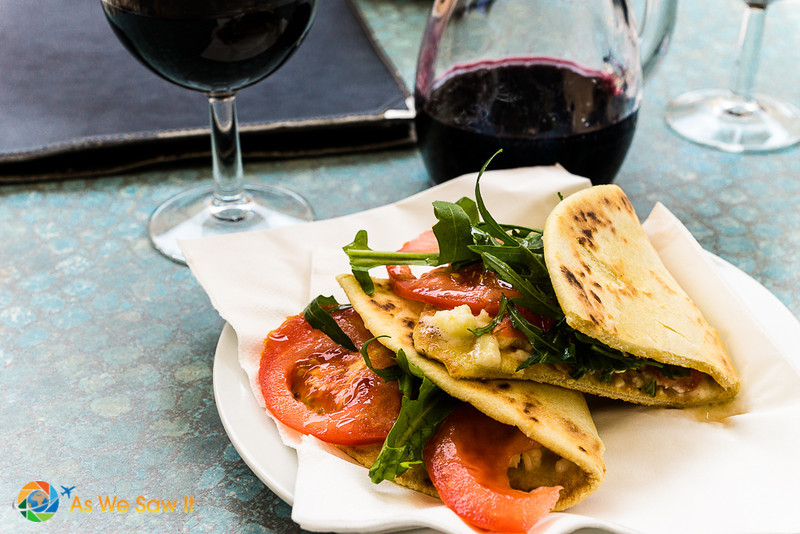 Piadina sandwich stuffed with rocket and tomatoes. Accompanied by a carafe of wine
