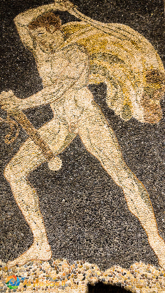 Ravenna mosaic of naked man wielding a cape behind his back and a rod in his left hand