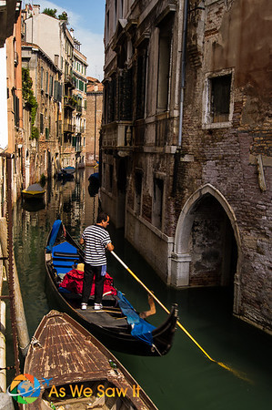 A gondolier makes his way home through a narrow canal.