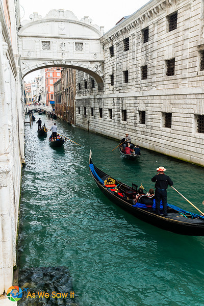 Gondoliers pass under the Bridge of Sighs. Two icons in Venice, Italy.