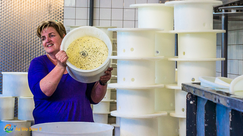 Woman holds up tub of cheese in a mold