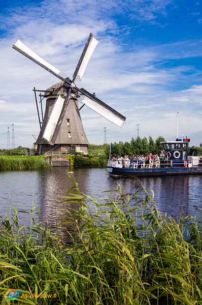 Canal boat passes one of the Dutch windmills on a canal at Kinderdijk