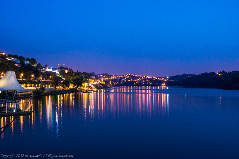 Lights on a bridge reflecting on the Douro River at twilight