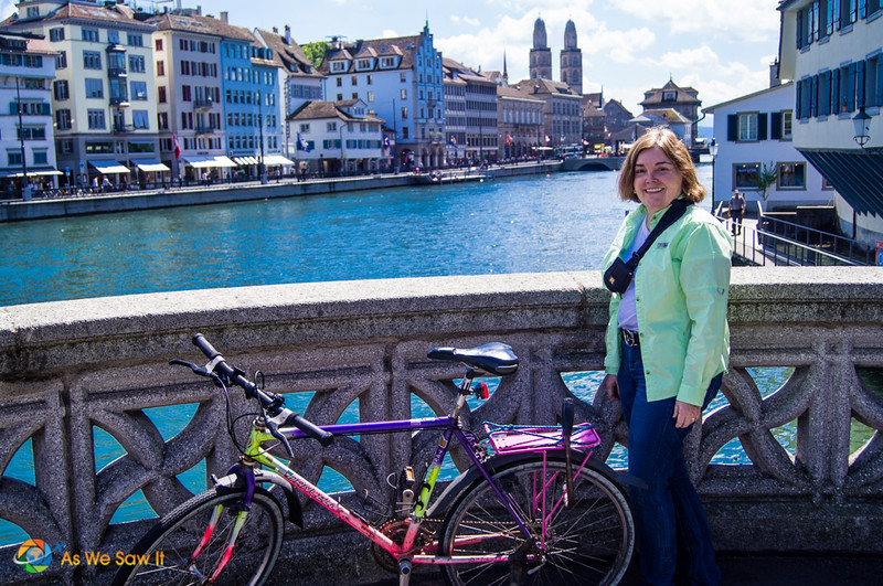 Linda standing next to a bicycle on a bridge in Zurich. River, church spires and city in background.