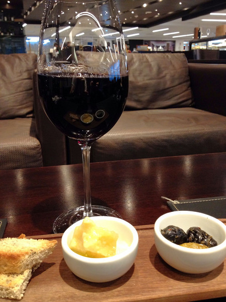 Glass of red wine and tapas board consisting of 2 bread slices, 3 bits of cheese and 3 olives on a table. Sofa in background