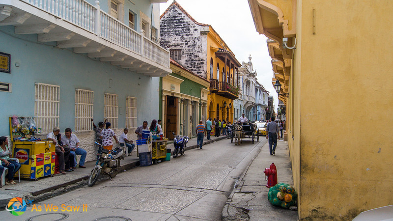 People sit along a street in old town Cartagena Colombia .