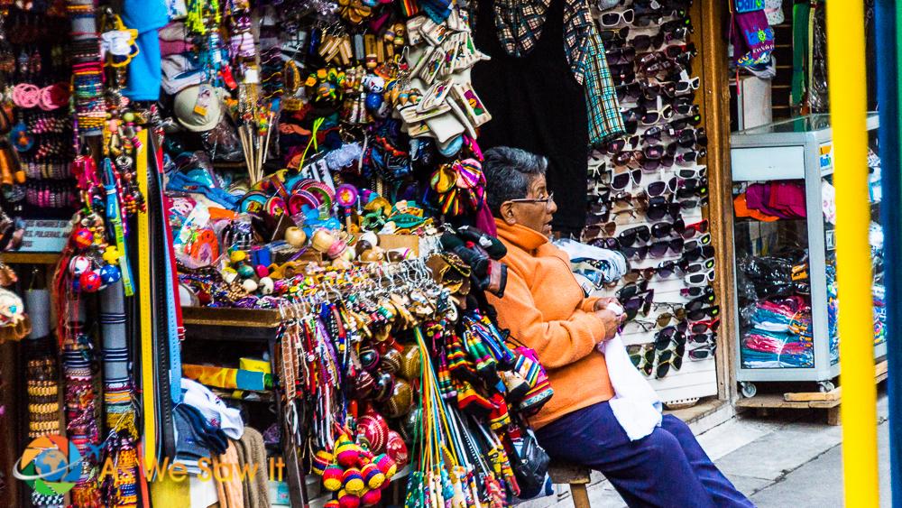 A vendor sits outside his souvenir shop