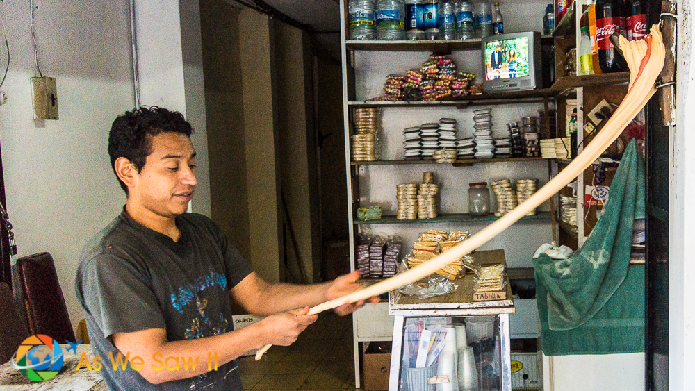 Pulling the traditional local taffy in the doorway of a shop in downtown Banos.