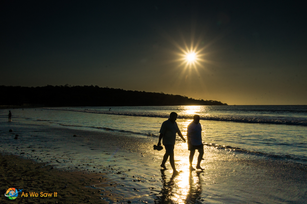 Two people walk along the beach in Jimbaran.