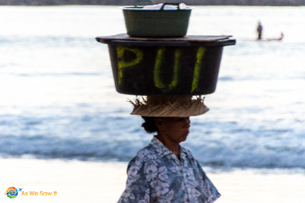 A woman sells food from the bin she carries on her head.