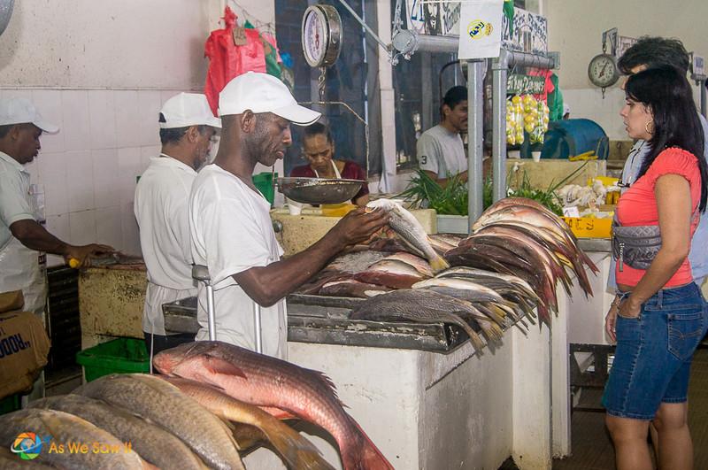 Mercado de Mariscos vendor picks up a fish that a woman just selected.