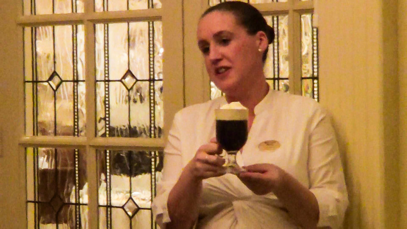 Waitress holding a glass of Irish coffee