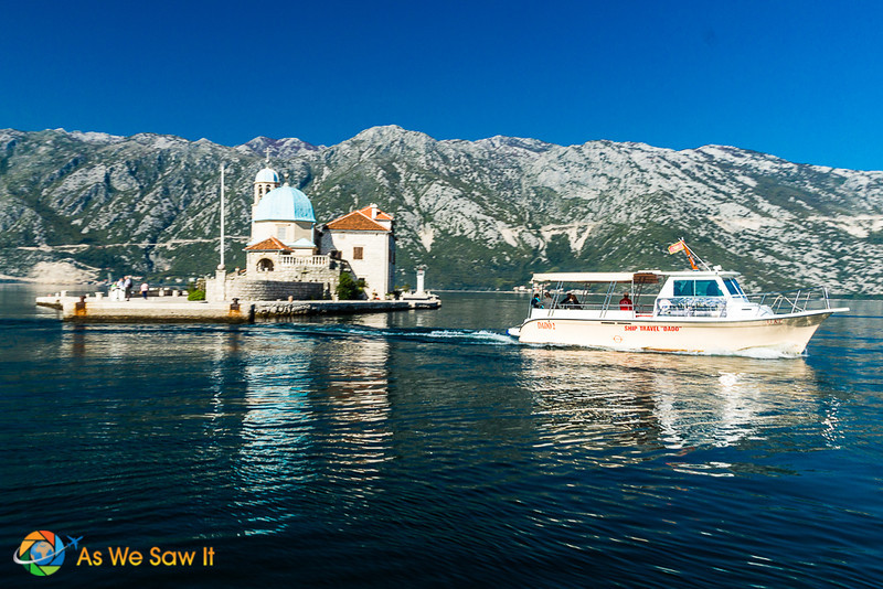 Tour boat leaves island on Bay of Kotor