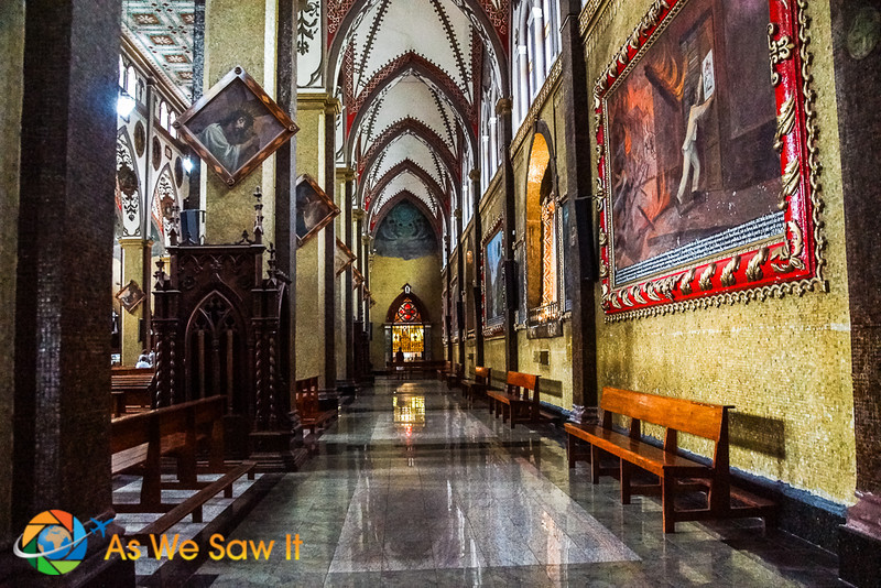 An aisle in Banos' Basilica, lined with paintings that portray miracles they attribute to Our Lady of the Holy Waters.