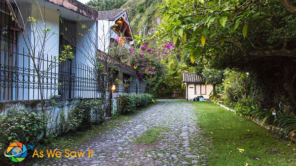 Cobbled driveway and parking area of Volcano Hotel in Banos, with a small garden