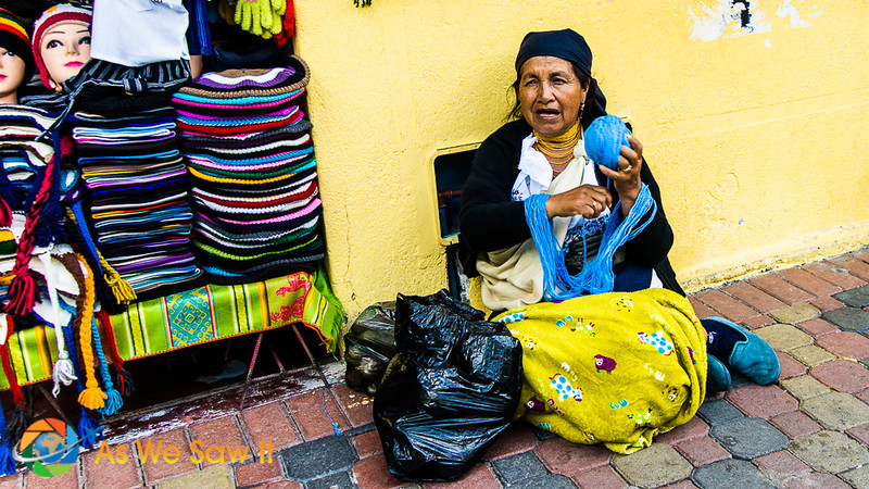 Ecuadorian woman sitting against the wall of her shop and chatting with her friend across the street. She's winding blue yarn to make hats.
